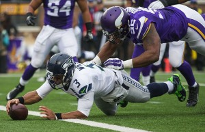 Russell Wilson falls into the end zone for a 2nd quarter touchdown Sunday against the Vikings. The Seattle Seahawks played the Minnesota Vikings Sunday, December 6, 2015 at TCF Bank Stadium in Minneapolis. (Dean Rutz / The Seattle Times)